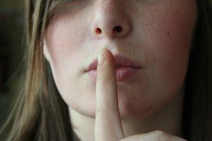doigt devant la bouche symbolisant l'argent tabou